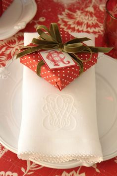 Red and white polka dot wrap with green velvet ribbon, monogrammed linens - Carolyne Roehm