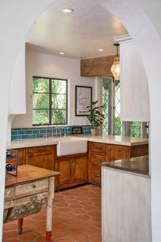 tera cotta; reclaimed island; farmsink; exposed beams: mediterranean kitchen by Style De Vie