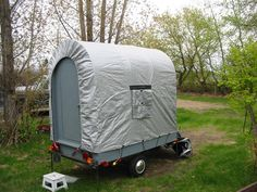 A variation on a covered wagon design, set up. Compact and low profile for towing, tilt up the end walls and deploy the canvas.