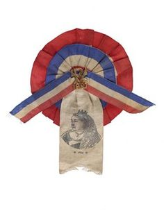 Souvenir rosette commemorating Queen Victoria's Golden Jubilee of 1897. A circular two tier, pleated rosette formed from red, white and blue ribbons, the broad central hanging ribbon printed with an image of the Queen. In the centre is a gilded metal pin marked 'VR 1897'. - See more at: http://collections.museumoflondon.org.uk/Online/object.aspx?objectID=object-64422&start=98&rows=1#sthash.X7E2iW86.dpuf