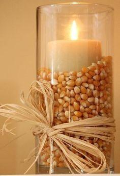 Vela en frasco de cristal, cilíndrico y alto, adornado con maíz de hacer palomitas y lazada de rafia.                                                                                                                                                      More