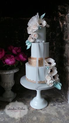 Beautiful pale grey wedding cake with blush sugar anemones, a rose gold sequin tier and a floating bottom tier trimmed with gold necklace detail