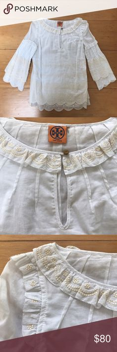 Tory Burch Embroidered T Logo Scalloped Tunic This beautiful tunic by Tory Burch is perfect for spring and summer! It is white with cream-colored embroidery (the T logo, which can be seen in some of the close-up photos). The ends of the shirt and sleeves are scalloped. The shirt has two thin 100% cotton layers to create a tier of scallops. The shirt is missing its size label but it is an XS/S. In excellent condition. Please let me know if I can answer any questions! 😊 Tory Burch Tops Tunics