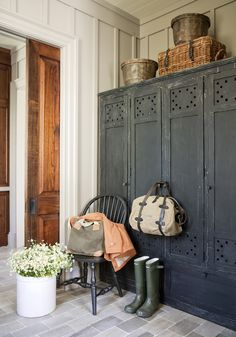 Gorgeous, tall cupboards in an entry/mudroom. I'm imagining shelves in some and hanging storage in others. I love the chair for sitting to put shoes and boots on as well as sitting items on when you walk in. The board and batten on the walls is pretty as well.