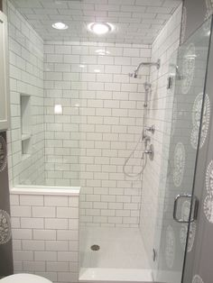 Tiling By Santana (.com)  Third Ward walk-in shower with half wall using white subway tile with contrasting grout running up to the ceiling. Niche and floor use penny round mosaic as an accent. The bench runs along the entire back wall and custom white slabs were installed for the half wall, curb, niche shelves, and seat.