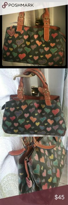 """Vintage Dooney & Bourke Hearts Purse Coated Canvas Authentic Dooney & Bourke. Vintage.  Coated canvas / Brown leather Shoulder bag. Black w multi color """"crayon hearts"""".  DB heart hang fob.  Nice overall vintage condition, showing some light fading.  Shiny gold hardware. 4 gold feet. Adjustable handles. Zipper closure, w 2 magnetic snap compartments.  M size bag.  Offers accepted.   13"""" Length  8.5"""" Height 4.5"""" Depth  6"""" Adjustable strap drop   Packaged with care, shipped quickly. Dooney…"""