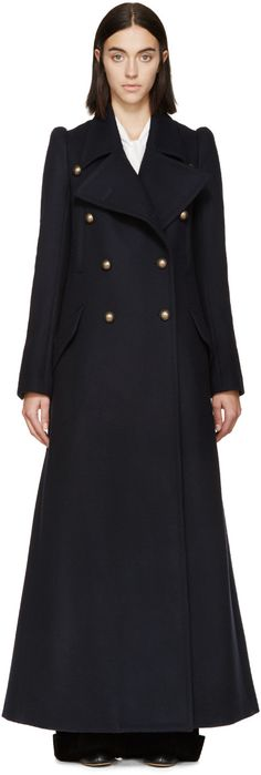 Long sleeve felted wool long coat in navy. Peaked lapel collar. Double-breasted closure at front featuring buttons in brass-tone. Welt and flap pockets at body. Five-button surgeon's cuffs. Extended vent at back hem. Partially lined. Tonal stitching.