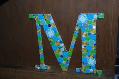 wooden letter M covered with buttons