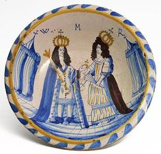 A LONDON DELFT BLUE DASH CHARGER OF WILLIAM & MARY, c.1690, with the Sovereigns standing between two pavilions and with 'WMR' above, 33cm diameter