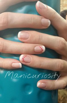 Gel polish white french with sweet pink accent dots on the ring finger is perfect for Valentine's Day.