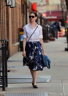 Anne Hathaway in a lady-like floral skirt, button-down, and flats