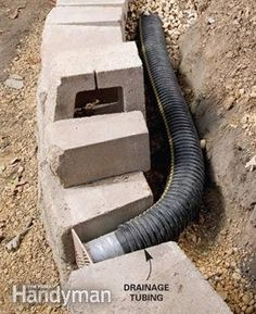 """Lay perforated drainage tubing at base. Water-soaked soil is the worst enemy of retaining walls because it exerts enormous pressure behind the wall. Adding good drainage behind block or stone walls is crucial for long-lasting, bulge-free walls. Start by laying perforated plastic drainage tubing along the base of the wall slightly above ground level so it can drain to daylight. Slope the tubing about 1/4"""" per foot."""