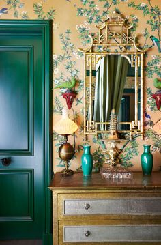 Delicious vignette by Hutton Wilkinson. Perfect hand painted gold chinoiserie wall paper with bird motif repeated by the porcelain birds placed on red stands on the walls. Gold bamboo pagoda mirror adds even more richness as does the gold and silver chest of drawers below. All this glistening gold is perfectly balanced by the cool and punchy deep emerald door to the left - gorgeous.