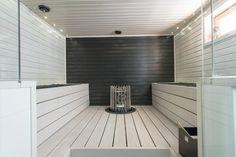 Valkoinen moderni sauna mustalla päätyseinällä