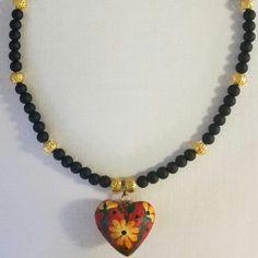 Collar  de cuentas negras opacas y cuentas doradas tipo filigrana con colgante de corazón de alebrije de madera y pintado a mano. #NaMeli