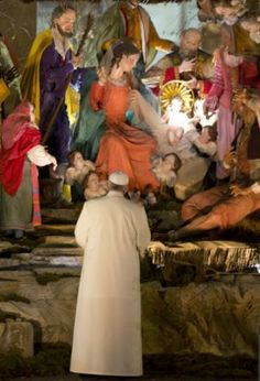 Pope Francis looks at the nativity scene set in St. Peter's square after celebrating a New Year's Eve vespers service in St. Peter...
