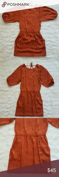 Michael Kors Dress Beautiful dress by Michael Kors. 3/4 sleeves. Elastic waist for support. Top fits loose. Bottom fits tight. Front side pockets. Size Medium.  Fabric content is 100% polyester.  It feels beautiful on the skin. Color is fire orange. Worn only one time, in excellent condition! Michael Kors Dresses