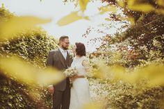 Bride & Groom stood in a garden, on their wedding day, amongst trees and flowers, at Wold Top Brewery in Yorkshire.