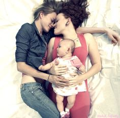 """lgbtgivesmehope: """" the-inspired-lesbian: """" ♡ """" [Image shows a lesbian couple lying down on bedsheets with their baby daughter] """" A wonderful image for International Women's Day. ^_^"""
