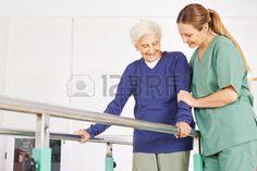 tercera edad: Fisioterapeuta ayudar Vieja mujer mayor en la cinta con asas Foto de archivo