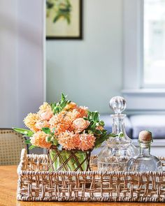 Floral designer Kirk Whitfield placed a peach-color floral arrangement, featuring hyacinth, ranunculus, and hellebores, in a woven tray beside a pair of crystal decanters. The room beyond, which boasts a tall window, is painted a soft pale green. Spring Flower Arrangements, Floral Arrangements, Spring Colors, Spring Flowers, Peach Colors, Bold Colors, Scented Geranium, Centerpieces, Table Decorations