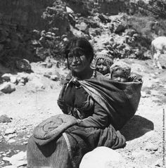 A native Peruvian Aymara Woman with a pair of twins in a sling on her back, 1950