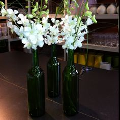 Wine bottle centerpieces with dendrobium orchids.  I made these for my wedding last summer.