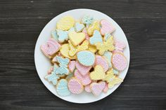 colorful easter cookies on white plate on dark gray table