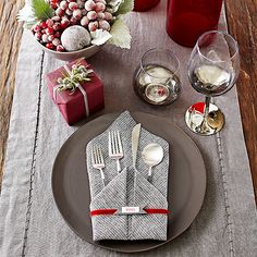 Want a touch of sophistication on your holiday table? This gray and wine-hue place setting has you covered. Plates, runners, and napkins coordinate in cool shades of silver and gray, and red vases and a small wrapped gift create warm contrast. We threw in a bowl of frosted red fruit, created by brushing with slightly beaten egg whites and sprinkling superfine sugar over the top, for powdery sparkle. Click below to download the free napkin banner and get our napkin-folding instructions.
