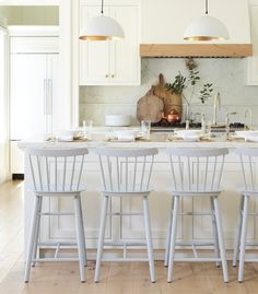 We love this white kitchen with a marble counter-top, gold-leafed light pendants, and classic wooden counter stools. We love this white kitchen with a marble counter-top, gold-leafed light pendants, and classic wooden counter stools. Kitchen Island Decor, Kitchen Counter Stools, Home Decor Kitchen, Kitchen Furniture, New Kitchen, Wooden Counter, Counter Top, White Counter Stools, Awesome Kitchen