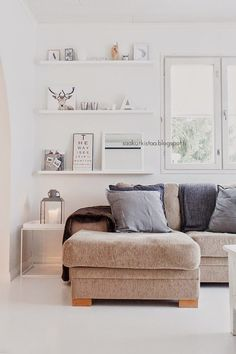 scandi vibes in this living room with wall-mounted floating shelves. minimal living room ideas
