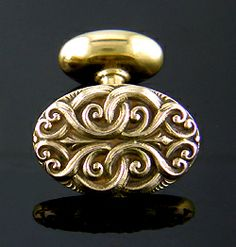 Elegant cufflinks with intricate, entwined scrolls.  The design is inspired by the foliate scrolls embellishing medieval tapestries and illuminated manuscripts.  You almost expect the leafy mask of the Green Man to peer out from behind the twisting vines.  Created by Carter, Howe & Co. in 14kt gold, circa 1900.