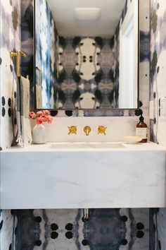 "Stunning powder room features walls clad in Eskayel Galileo Glass Indigo Wallpaper lined with a marble floating sink vanity under a gold wall mount faucet, Purist Widespread Wall-Mount Bathroom Sink Faucet Trim with 6"", and a rectangular vanity mirror."