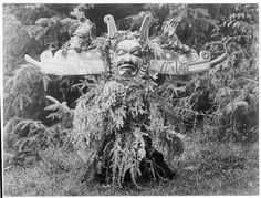 Ceremonial Dress of the Kwakiutl and Nootka Tribes of British Columbia, 1914 - Sisiutl, one of the main dancers in the Winter Dance ceremonies, wearing a double-headed serpent mask and shirt made of hemlock boughs