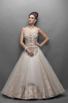 This offwhite color Indo western bridal gown has luminous satin base with a graceful gatthering of net & lace in the flair. The bodice is replete in pearly beads & gold and silver crystal embellishmen