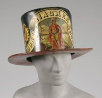 LabelIn the early nineteenth century the disciplined and heroic volunteers at Philadelphia's several dozen fire companies wore special hats to identify themselves. Modeled on fashionable stovepipe hats but made in leather to withstand heat and water, these hats were also proudly worn at pumping contests and when marching in parades. Fire companies carefully selected their names and painted symbols; these included Ben Franklin, founder of the first fire company in 1736.circ 1838