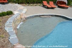 Sun Shelf out of Gunite with Pebble Finish and Sea Shell Accent - hand carved stone step down into the pool. Spillover sheer decent waterfall in the raised retaining wall that also serves as the pool wall, capped with bluestone.     Vinyl Liner Pool and Gunite Pool Combination. Michigan Custom Hybrid Swimming Pool