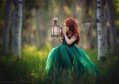 Фото Рыжеволосая девочка в зеленом платье стоит в лесу с фонариком в руке, фотохудожник Lisa Holloway