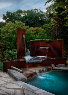 A stellar water feature comprised of Corten steel is the focal point of this patio and pool area by AguaFina Gardens International. At night, soft landscape lights illuminate the metal sculptures and so evoke thoughts of modern artwork.