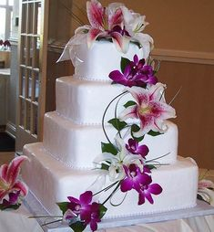 Square four tier white fondant wedding cake decorated with tropical flowers, like purple orchids, white oriental lillies and pink tiger lillies. From Manassas Cakery www.flickr.com