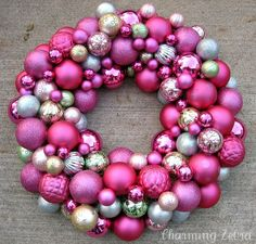 Pink Ornament Wreath -- Wrap a ribbon around the top of the form to create a loop for hanging. Hot glue ornaments in various shades and sizes to the straw/foam wreath form.