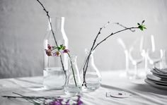 Make a dining centerpiece using bare branches and glass vases.