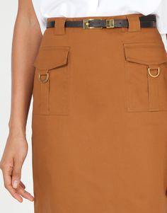 Falda recta largo rodilla con cremallera en espalda y forro. Bolsillos de inspiración safari con hebillas doradas y cinturón de símil pie