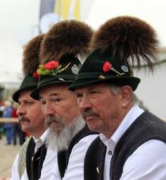 Bavarian men in traditional attire watch a parade to celebrate 200 years of Oktoberfest