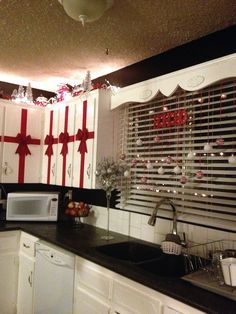 Red, white, black and silver Christmas in the kitchen. Rolls of red velvet ribbon and bows from the dollar store. A total of $12 did all 14 of my upper cupboards.