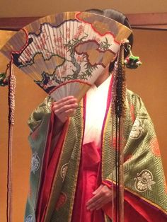 A woman hiding her face with a hiogi (cypress wood fan) which was a necessity during the heian era.