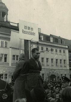 """German woman and Polish man are forced to carry posters reading """"I have had relations with a Pole"""" and """"I am a race defiler."""" Eisenach, Germany, November 1940"""