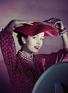 1955 A model uses a hat pin to secure a wide-brimmed, pink, straw hat, trimmed with velvet.