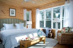 I don't usually like knotty pine, but this is beautiful with all the white trim, curtains and bedding - I'd use even more.