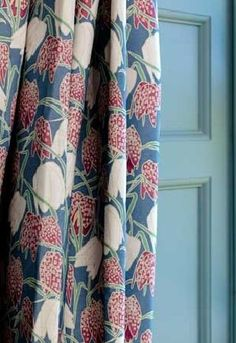 Emily Burningham Fabric Collection. Curtain with mid-blue background and bold white and pink flowers with light green foliage.
